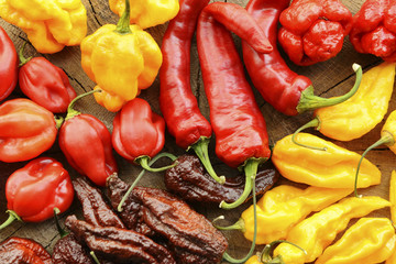Various hot peppers viewed from the top on a wooden background. Wall mural