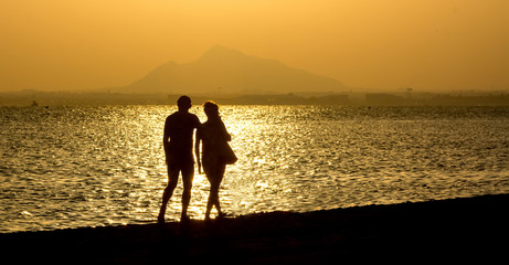 romantic stroll along the beach at sunset couple