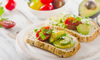 Homemade sandwiches with sliced avocado and tomato.