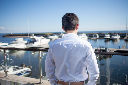 young man near the yacht club,  view from  back