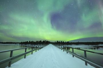 Fototapete - Aurora borealis over a bridge in winter, Finnish Lapland
