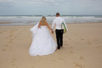 Rear view wedding couple at the beach going to surf for fun