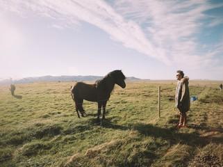 man in front of beautiful black islandic horse