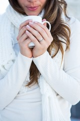 Brunette with warm clothes drinking coffee