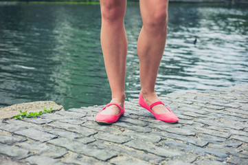 Legs and feet of young woman by canal