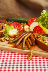 Stew in pot on wooden plank. Various vegetable, meat and sausages. Traditional cuisine.