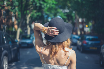 Young woman with hat walking in the street