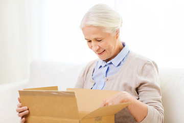 happy senior woman with parcel box at home