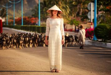 blonde girl in Vietnamese dress stands against defocused flock