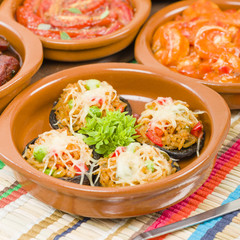Stuffed Mushrooms - Mushrooms topped with cooked spicy rice and cheese. Surrounded by other tapas dishes.