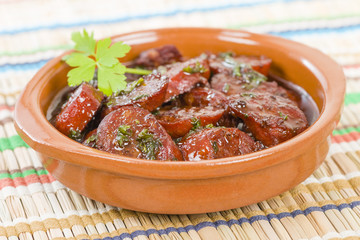 Chorizo al Vino (Spicy sausage cooked in red wine). Traditional Spanish tapas dish.