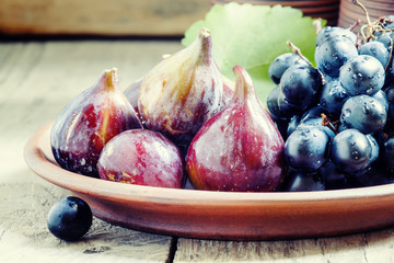 Ripe figs and grapes on a clay plate in a rustic style, selectiv