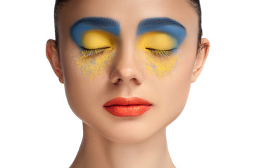 High fashion look, closeup beauty portrait of beautiful young woman model with bright makeup with perfect clean skin with colorful red lips and blue yellow eyeshadows, blue yellow color. High key.