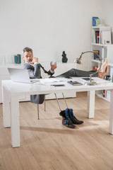 Portrait of a grey hair business man sitting at his desk in a lu