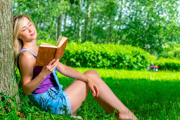 young blond woman reading a novel in the park sitting near a tre