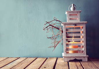 low key image of white wooden vintage lantern with burning candle and tree branches on wooden table. retro filtered image