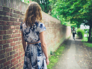 Young woman walking in the street by wall