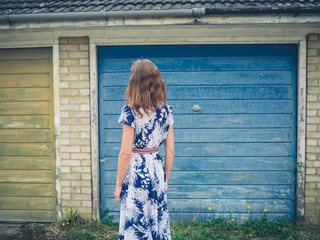 Young woman in dress standing outside garage