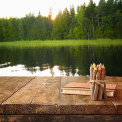 vintage notebook and stack of wooden colorful pencils on wooden texture table in front of countryside lake and forest view