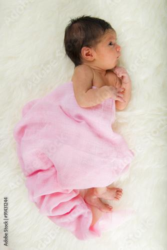 Niña bebé recién nacido en calma relajada sobre una manta de pelo suave con  muselina rosa 42202f76376
