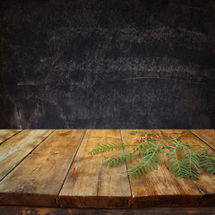 front image of wooden table and autumn leaves in front and blackboard background with room for text