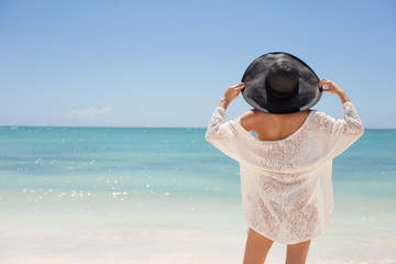 Woman in summer hat on the beach