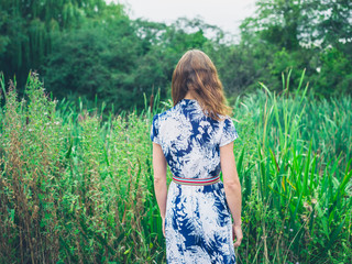 Young woman in dress by tall grass