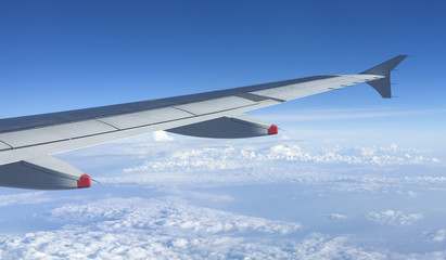 Wing of the plane on blue sky, travel concept background.