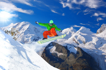 Wall Mural - Snowboarder jumping against blue sky in Swiss Alps
