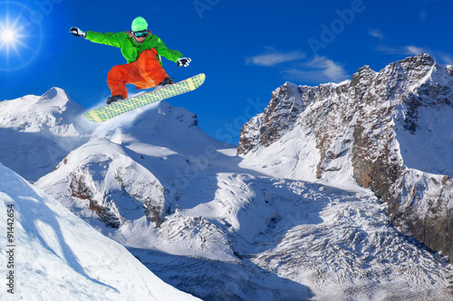 Wall mural Snowboarder jumping against blue sky in Swiss Alps