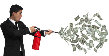 Business man putting out a fire with money