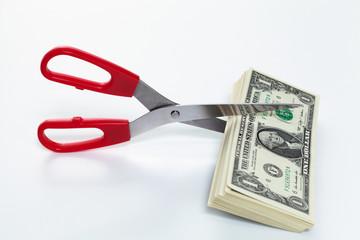scissors cutting dollar bills
