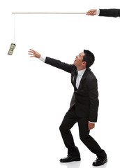 Exhausted Businessman reaching for money on the end of a stick