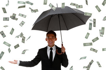 Raining money on a businessman holding an umbrella
