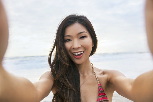 Asian Woman Girl at Beach Taking Selfie Photograph