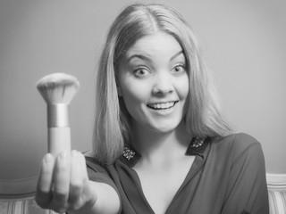 Attractive woman holding powder brush. Make up.