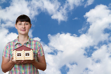Girl holding a house on a background of sky