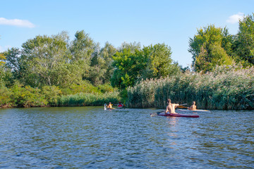 boys paddle canoes on the river