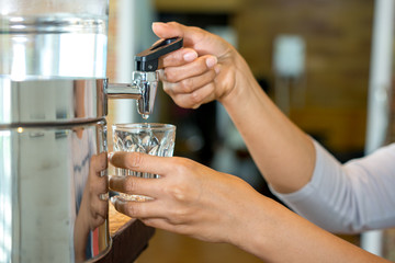Woman hand pouring water in to clear glass