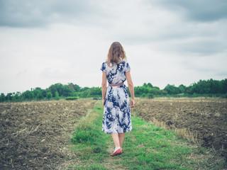 Young woman walking in barren field