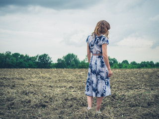 Young woman standing in barren field on cloudy day