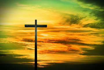 Christian cross on green and yellow sunset background