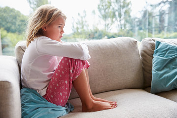 Unhappy Young Girl Sitting On Sofa At Home