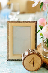 Wooden photo frame like decoration on the table for wedding in rustic style