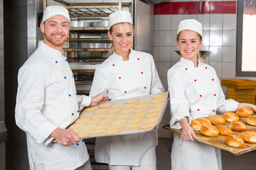 Baker presenting tray with pastry or dough at bakery