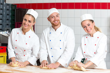Three bakers in bakery kneading fresh dough