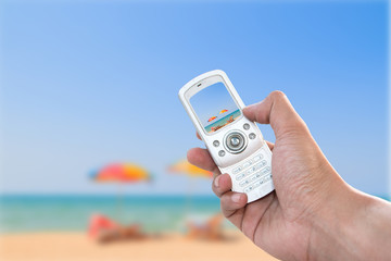 Human hand holding vintage phone shooting picture at the sea with image of blurred colorful umbrella
