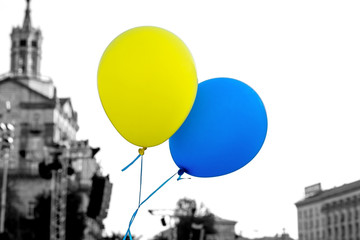 Flying balloons with colors of flag of Ukraine in city center