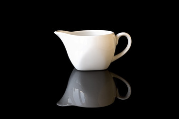 White gravy boat on a black mirror background