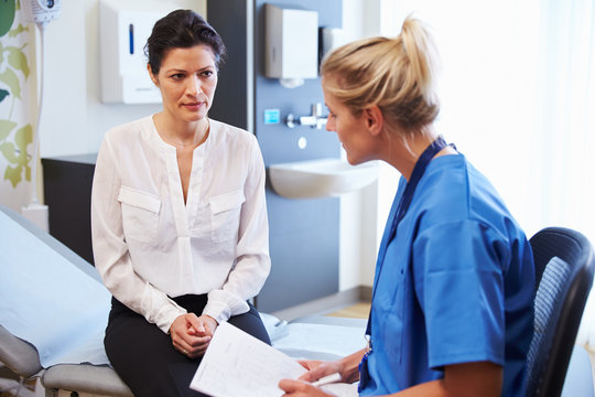 Female Patient And Doctor Have Consultation In Hospital Room